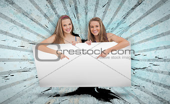 Pretty girls pointing to copy space card