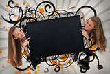 Girls pointing to black copy space on artistic swirl design background