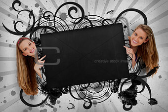 Girls pointing to black copy space with artistic swirl frame