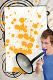 Young man shouting through megaphone in front of copy space with yellow paint splashes