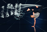 Martial arts expert doing hand stand against broken glass background