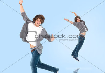 Two of the same teenage boy jumping for joy