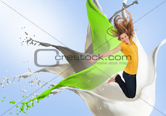 Pretty young woman jumping for joy with artistic paint splashes