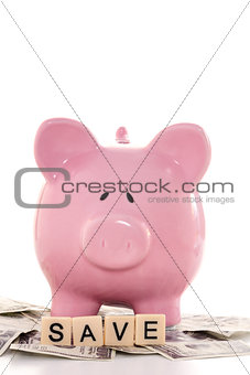 Close up of a piggy bank and save spelled out in plastic letters pieces