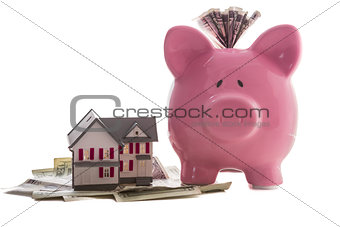 Close up of a pink piggy bank with dollars beside miniature house model