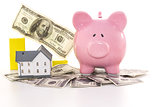 Pink piggy bank beside miniature house and graph