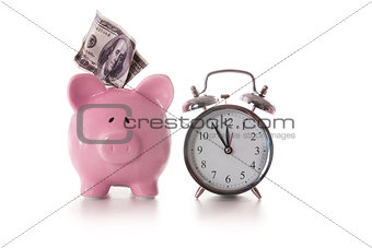 Alarm clock and piggy bank with dollar sticking out