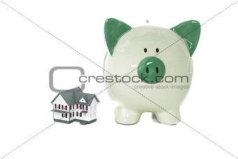 Green piggy bank standing beside miniature home