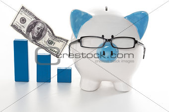 Blue and white piggy bank wearing glasses with blue graph model