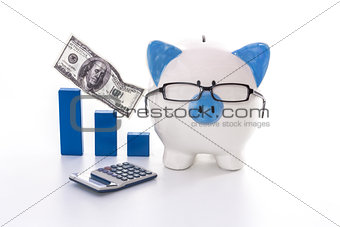 Blue and white piggy bank wearing glasses with blue graph model and calculator