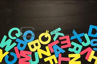 Alphabet magnets in a jumble on blackboard