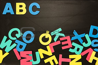 Alphabet magnets in a jumble on blackboard with Abc in order