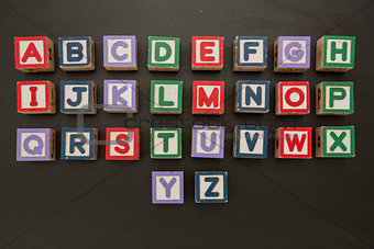Alphabet blocks on blackboard