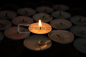 Single candle lighting surrounded by others