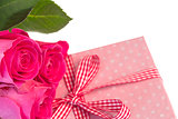 Pink roses leaning on pink polka dot wrapped present