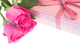 Pink roses resting on pink polka dot wrapped present with copy space