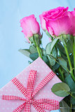Bouquet of pink roses in vase with pink gift