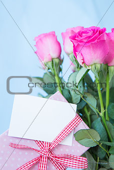 Bouquet of pink roses in vase with pink gift and blank card