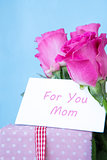 Bouquet of pink roses in vase with pink gift and mothers day card