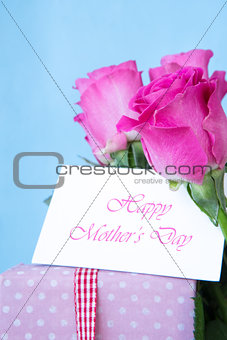 Bouquet of pink roses with pink gift and blank card