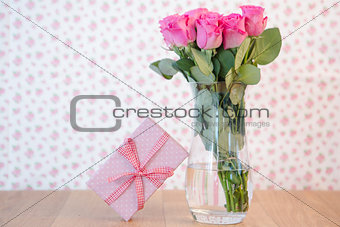 Bouquet of pink roses in vase with pink gift leaning against it