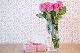 Bunch of pink roses in vase with pink gift and blank card
