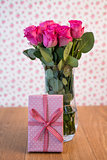 Bunch of pink roses in vase with pink gift leaning against it