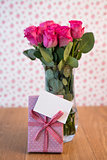 Bunch of pink roses in vase with pink gift leaning against it and blank card