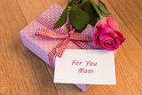Pink wrapped present with mothers day card and pink rose