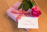 Pink wrapped present with happy mothers day card and pink rose