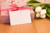 Pink wrapped present with bunch of white tulips and blank card