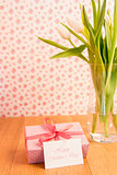 Pink wrapped present with mothers day card beside vase of tulips