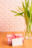 Pink wrapped present with blank card beside vase of tulips