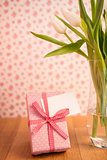 Vase of tulips on wooden table with pink wrapped gift and blank card