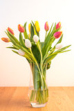 Vase of tulips on wooden table