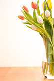 Glass vase of tulips on wooden table