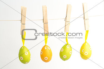Four easter eggs hanging from a line