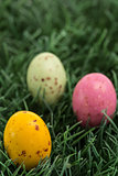 Three small easter eggs nestled in the grass