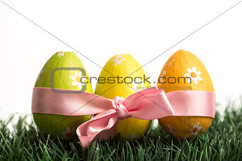 Three easter eggs wrapped in pink ribbon