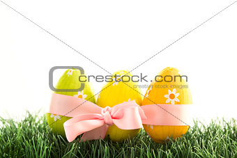 Three easter eggs wrapped in pink ribbon with a bow