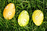 Three easter eggs nestled in the grass
