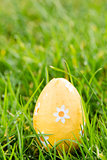 Orange easter egg sitting in the grass