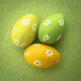 Three foil wrapped easter eggs on green surface