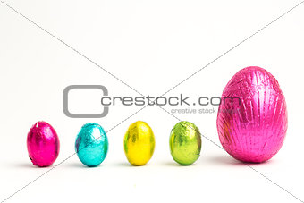 Four small easter eggs beside large one