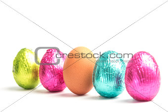 Four easter eggs in a row with one real egg