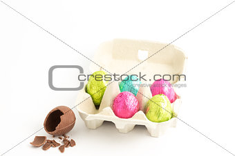 Carton of easter eggs with one broken on surface