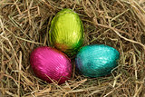 Three easter eggs nestled in straw