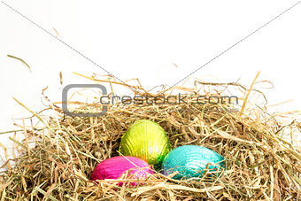 Three easter eggs nestled in straw nest
