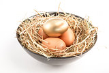 Three eggs in a black bowl with one gold one