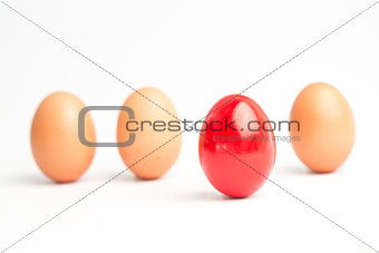 Four eggs in a row with one red one standing out